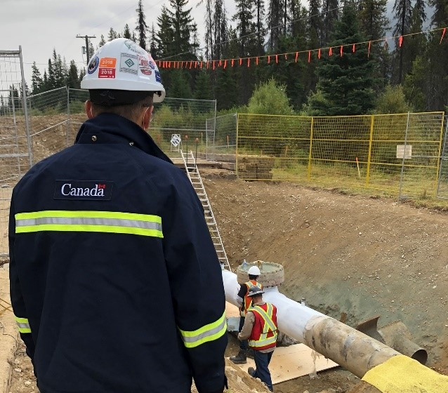 A CER inspector observes work on a section of pipe being prepared for reactivation at a Trans Mountain site in Jasper, Alta.
